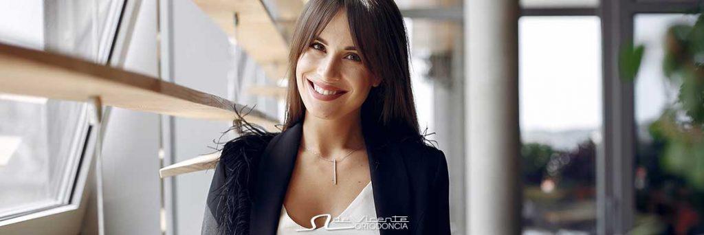 mujer sonríe con aparato de ortodoncia invisible Invisalign