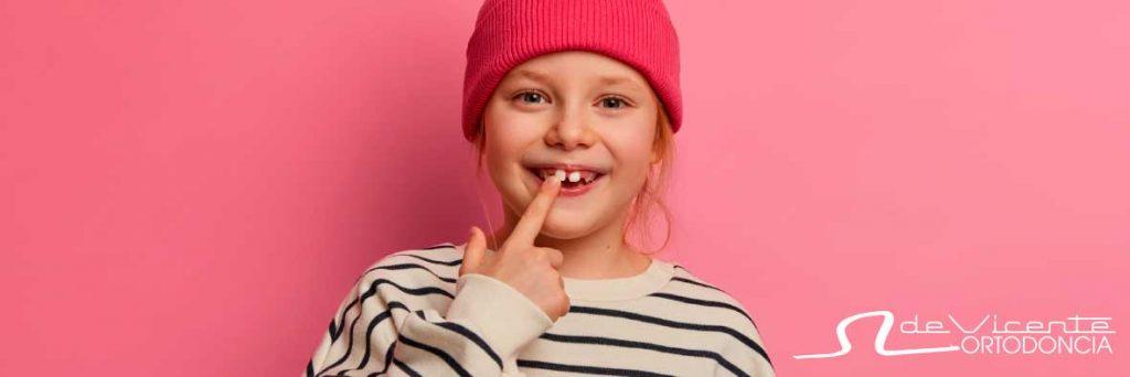 niña sonriendo para mostrar los dientes antes de tratamiento de ortodoncia infantil