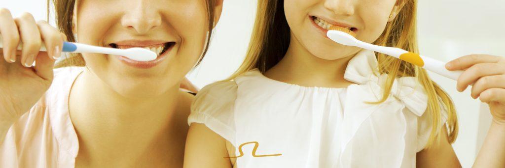 madre e hija se cepillan los dientes para cuidar que el tratamiento de ortodoncia De Vicente granada funcione