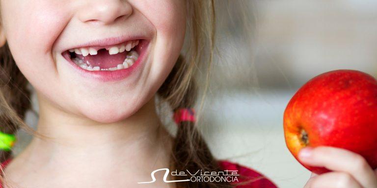boca de nina sonriente a la que le falta un diente