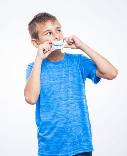 ortodoncia infantil y niño jugando con aparato de dientes en Granada